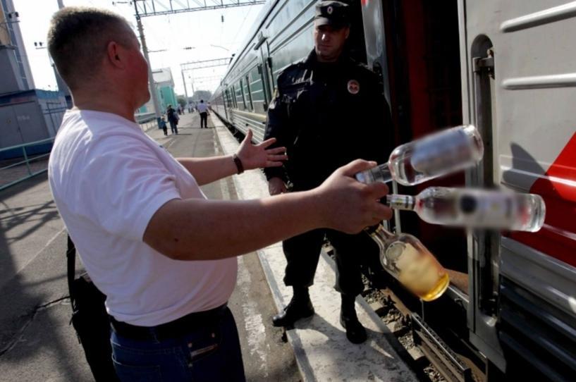 Мужчина держит несколько бутылок со спиртным
